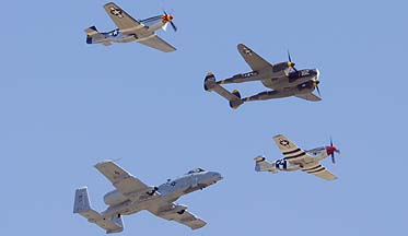 Lockheed P-38J Lightning NX138AM 23 Skidoo, North American P-51D Mustang NL5441V Spam Can, P-51D Mustang NL7715C Wee Willy II, and Fairchild-Republic A-10A Thunderbolt II of the 355th Fighter Wing